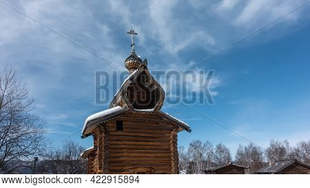 The Old Chapel Was Built Of Unpainted Logs. Domes And Cross Against The Blue Sky. Snow On The Roof.