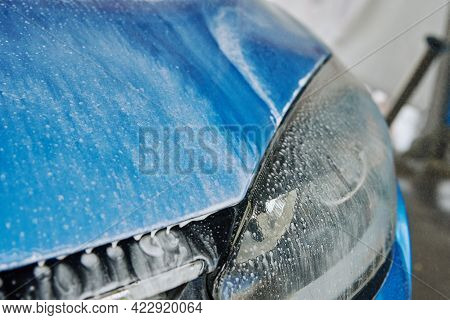 Car Washing. Soap Water Running Off From A Washed Blue Car. Cleaning Car With Contactless High Press