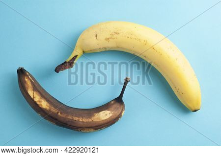 Minimal Flatlay Concept Made Of Ripe And Rotten Bananas On Blue Background