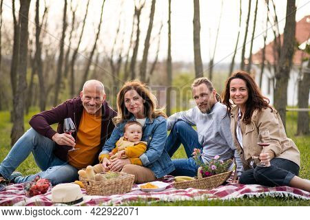 Happy Multigeneration Family Outdoors Having Picnic In Nature.