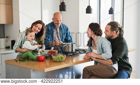 Happy Multigeneration Family Indoors At Home Cooking Together.