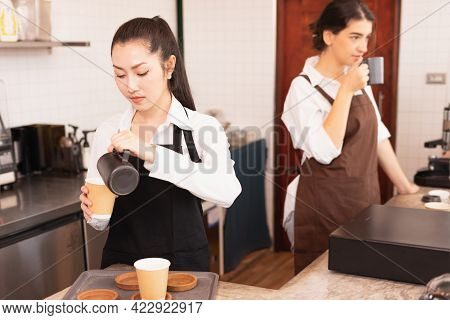 Asian Barista Women Fill Milk Into Takeaway Hot Coffee Cup For Customer While Caucasian Barista Woma