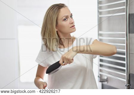 Woman Combing Her Hair With Comb In Bathroom In Front Of Mirror