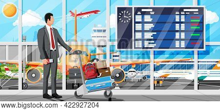 Man And Hand Truck Full Of Bags In Terminal Interior. Arrival Departure Board. Airport Luggage Troll