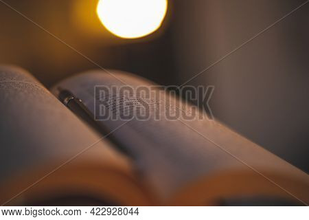 Closeup Photo of an Open Book with A Pen. Reading An Interesting Novel at the Evening at Home. Leisure Time at Home.