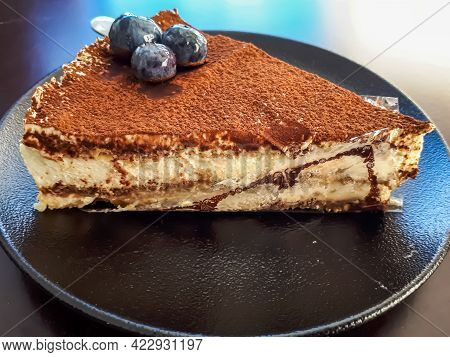 Triangular Piece Of Italian Dessert - Tiramisu Cake Decorated With Blueberries On A Dark Plate On Da