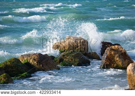 Splashing Waves On The Seashore With Stones