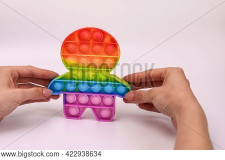 Hands Holding A Colored Toy Antistress Pop It. On A White Background, Close-up.