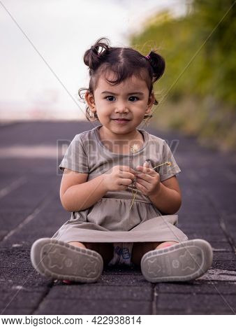 Cute Little Girl Sitting On The Promenade Near The Beach. Warm Sunny Day. Summer Vacation. Holiday C