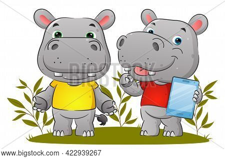 The Couple Of The Hippopotamus Is Holding The Tablet And Explaining Something In The Garden Of The I