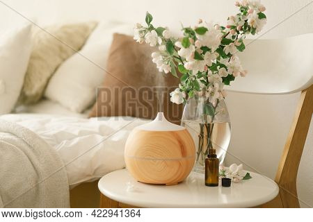 Aromatherapy Concept. Aroma Oil Diffuser On Chair Against In The Bedroom. Air Freshener.