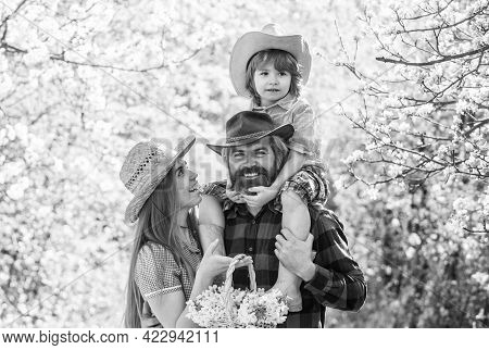 Farmers In Blooming Garden. Parents Growing Little Baby. Spend Time Together. Lovely Family Outdoors