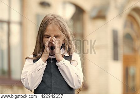 Small Kid With Blond Hair Wearing School Uniform Give Long Yawns In Schoolyard, Morning