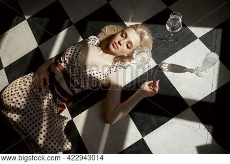 Woman With Glass Alcohol In Hand Lies On Floor, An Old Interior, Romantic Look Blonde Girl. Shadow O