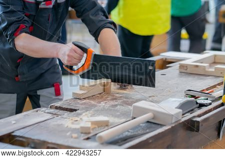 Professional Man Carpenter Using Hand Saw To Cutting Wood On Workbench At Workshop - Close Up. Carpe