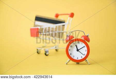 Red Analog Clock With Blurred  Shopping Cart And Gold Credit Card On Yellow Background , Cashless So
