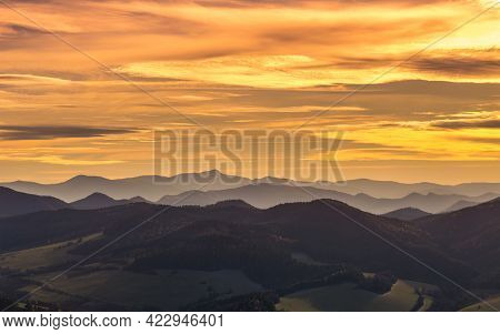Mountains Colored In Shades Of Orange At Sunset In Autumn. The Ridges Of The Mountains Are Condensed