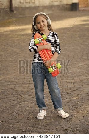 Little Child Hold Penny Skateboard Listening To Music In Modern Headphones Summer Urban Outdoors, Sp