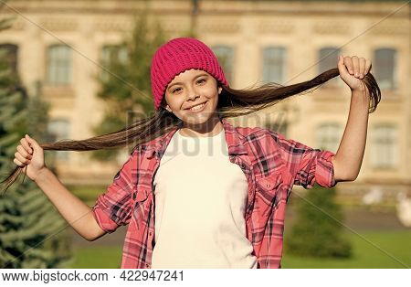 Treat Your Hair Today. Happy Girl Hold Long Hair Outdoors. Beauty Look Of Little Child. Hair Salon.