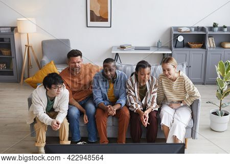 Wide Angle View At Multi-ethnic Group Of Friends Watching Tv At Home Together While Sitting In Row O