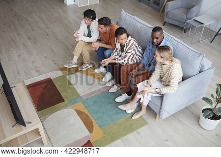 Top View At Multi-ethnic Group Of Friends Watching Tv At Home Together While Sitting In Row On Sofa,