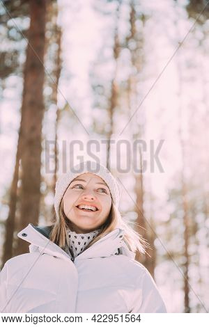 Portrait Of Young Pretty Caucasian Happy Girl Woman In White Jacket And Hat Posing In Winter Forest