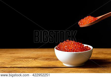 Red Caviar In A Wooden Cup On A Black Background With A Spoon. A Large Pile Of Bright Caviar. Fresh