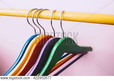 Set Of Several Bright Multicolored Wooden Clothes Hangers Hang On A Yellow Rack On A Pink Background