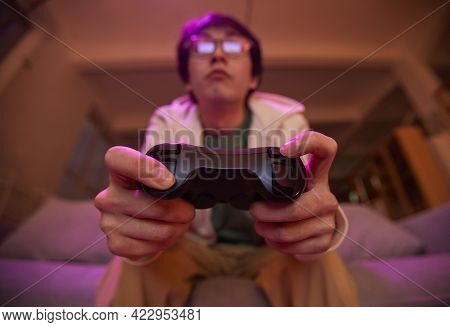 Low Angle View At Asian Young Man Holding Gamepad And Playing Video Games At Home Lit By Purple Ligh