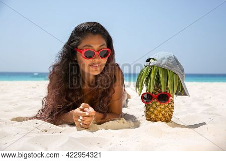 Ripe And Juicy Pineapple In A Cap And Red Sunglasses Stands On The Beach Near With A Beautiful Girl