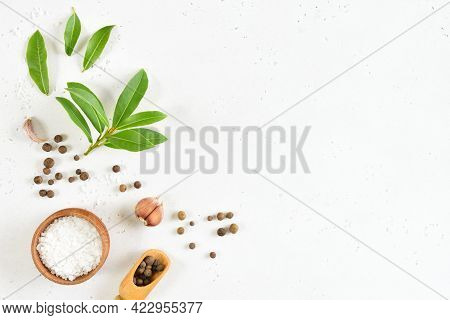 Fresh Bay Leaf, Allspice And Garlic On White Stone Background With Copy Space. Top View, Flat Lay