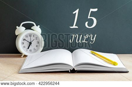 July 15. 15-th Day Of The Month, Calendar Date.a White Alarm Clock, An Open Notebook With Blank Page