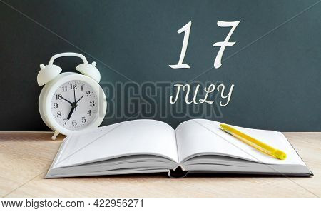 July 17. 17-th Day Of The Month, Calendar Date.a White Alarm Clock, An Open Notebook With Blank Page