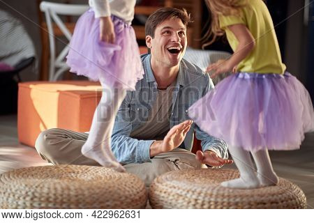 A young happy father is drumming while his little daughters dancing in a cheerful atmosphere at home. Family, together, playtime, home