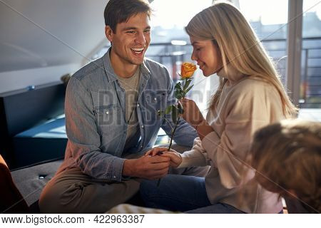 Young spouses enjoying a smell of the rose on Valentine's day in a romantic atmosphere at home. Family, love, together, home