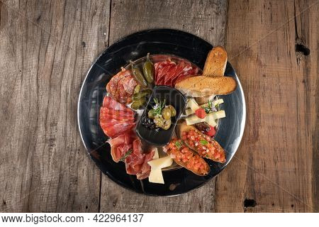 Top view of an assortment of cold appetizers served on a black plate isolated on rustic wooden table