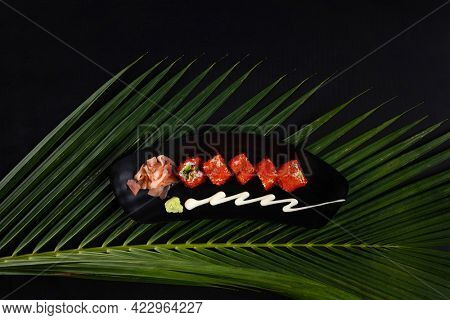 Top view of deep-fried prawns, avocado, mayonnaise and tobiko sushi isolated on black table with tropical leaves