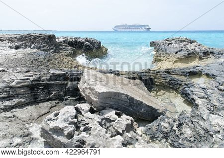 The View Of Half Moon Cay Island Rocky Coastline And A Cruise Ship In A Background (bahamas).