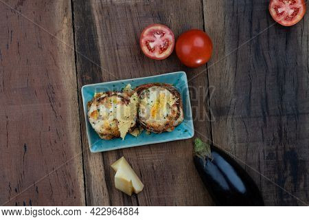 Top view of pan fried crispy eggplant with parmesan cheese crust isolated on wooden table