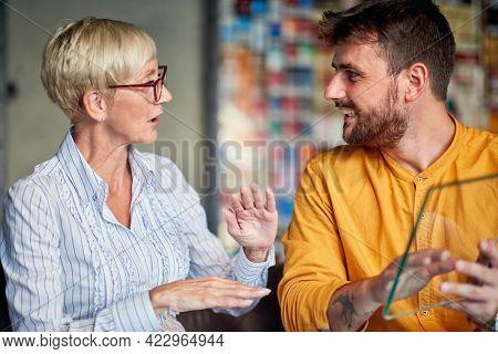 Senior female partner mentoring joyful businessman in the office