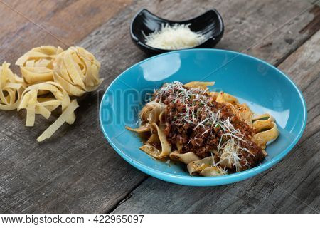 Spicy pasta Bolognese with fettuccini pasta isolated on the wooden table