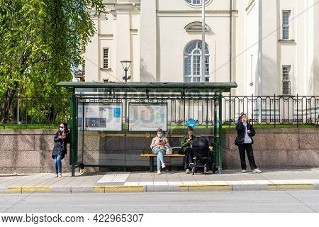 Stockholm, Sweden - May 25, 2021: Front View Of People With Face Masks Waiting At A Bus Stop In Stoc