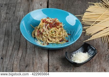 Traditional Italian pasta dish, spaghetti carbonara with bacon, yolk, parmesan cheese on a plate isolated on wooden table