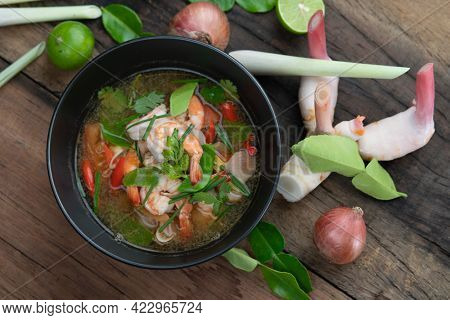 Traditional spicy prawn soup with galangal, lemongrass, kaffir lime leaf and straw mushrooms isolated on the wooden table
