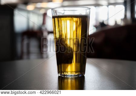 One Backlit Full Glass Pint With Golden Amber Beer On Table In A Dark Pub.