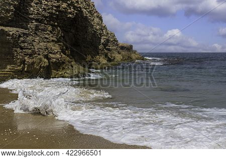 White Sea Foam On The Mediterranean Sea Coast Against The Backdrop Of A Textured Cliff