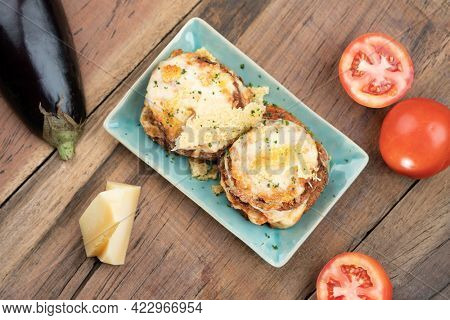 Pan fried crispy eggplant with parmesan cheese crust isolated on wooden table