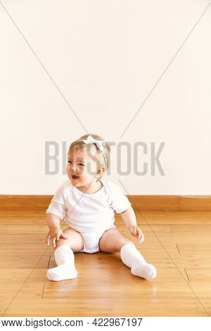 Little Laughing Girl With A Bow On Her Head Sits On The Floor In The Room