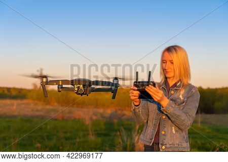 Young Blonde Woman Controls A Drone In Nature During Sunset. In The Foreground Is A Close-up Drone