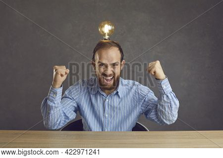Funny Crazy Man With Idea Light Bulb On Head Sitting At Desk And Shouting Eureka